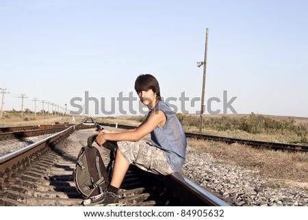 Teen boy on rail road - stock photo