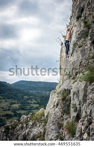 Teen boy rock climbers to the top
