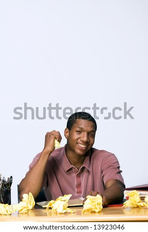 Teen boy seated at a desk smiling. There are  folders, pens, pencils, and crumpled paper on the desk. Horizontally framed photograph - stock photo