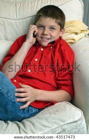 teen boy sitting in chair talking to a friend on his cell phone