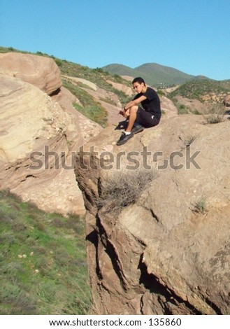 teen boy sitting on cliff against blue sky - stock photo