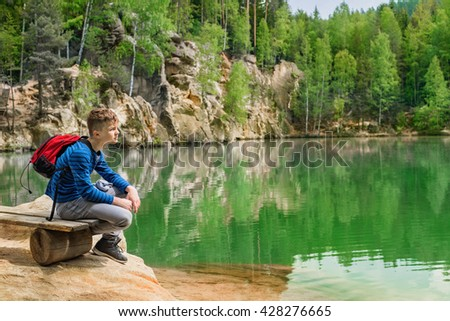 Teen boy sitting on the shore of Piskovna lake. National Park of Adrspach-Teplice rocks. Rock Town. Czech Republic.