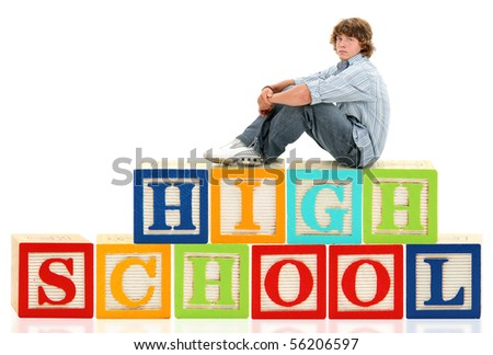 Teen boy sitting on the word high school in giant alphabet blocks. - stock photo
