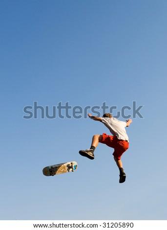 teen boy skateboarder making a high jump - stock photo