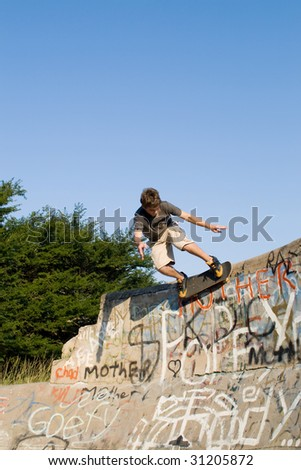 teen boy skateboarder playing on concrete ramp - stock photo