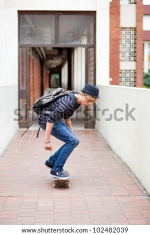 teen boy skateboarding in school passage - stock photo