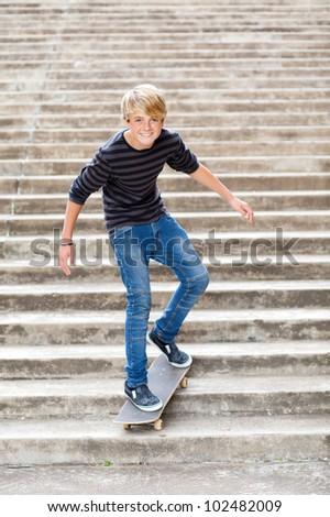 teen boy skateboarding on stairs - stock photo