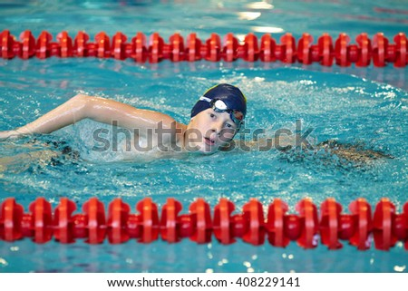 Teen boy swimming in the pool at the training in swimming