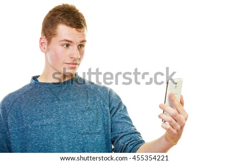 Teen boy texting on the mobile phone. Young man reading sms on smartphone surprised face expression isolated