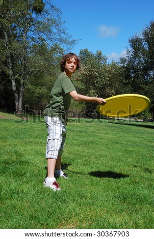 Teen boy throwing yellow frisbee with green grass, trees, and blue sky in the background.