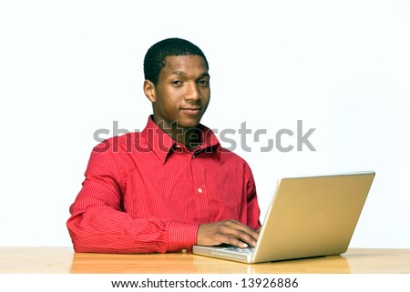 Teen boy types on a laptop computer as he sits at a desk and looks serious. Horizontally framed photograph