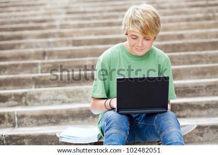 teen boy using laptop outdoors - stock photo