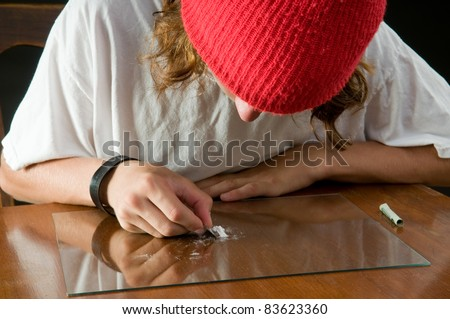 teen boy using razor to make a line of cocaine - serious drug abuse - stock photo