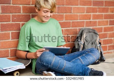 teen boy using tablet computer in school - stock photo