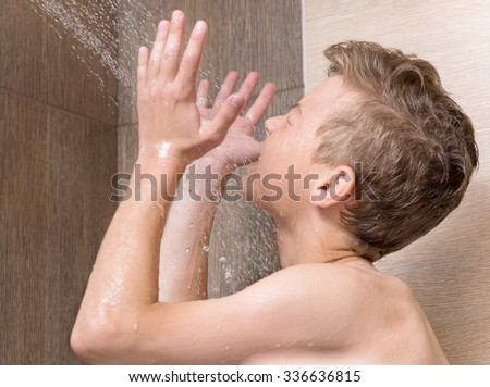 Teen boy washing face and body in shower in the bathroom - stock photo