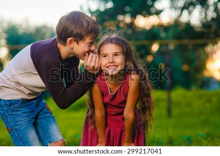 Teen boy whispering secret gossip girl child's ear to the street, and the summer sun sunset photo for your website - stock photo