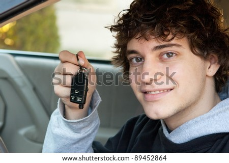Teen boy who just got his driver's license holding keys in the car - stock photo
