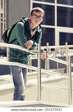 Teen boy with backpack against a school building - stock photo