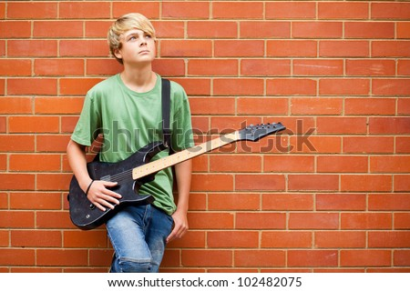 teen boy with guitar daydreaming - stock photo