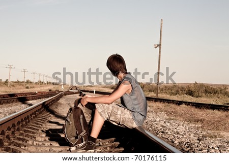 Teen boy with problems siting on rail road - stock photo