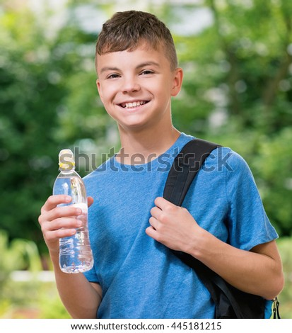Teen boy 12-14 year old with schoolbag and bottle of fresh. Student teenager posing outdoors.