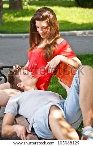 Teen boyfriend lying on his girlfriend's lap - stock photo