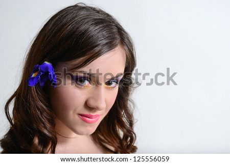 teen closed her eyes. makeup and iris flower - stock photo