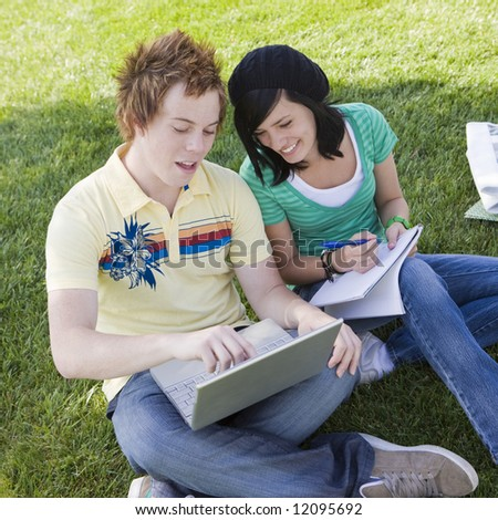 Teen couple do homework in the grass - stock photo