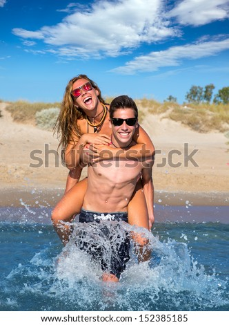 Teen couple enjoying  piggyback on summer beach shore splashing water - stock photo