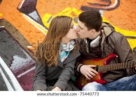 Teen couple kissing at graffiti background. - stock photo