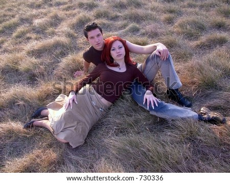 Teen couple laying in grass - stock photo