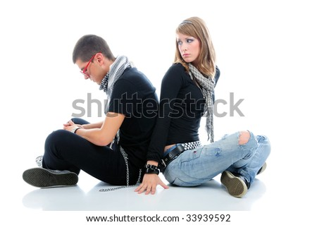 Teen couple sitting down with sad expression on their faces, isolated on white - stock photo