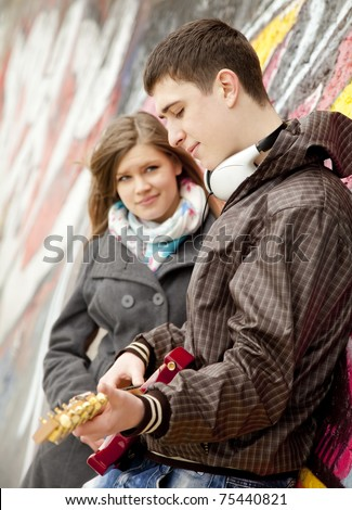 Teen couple with guitar at graffiti background. - stock photo