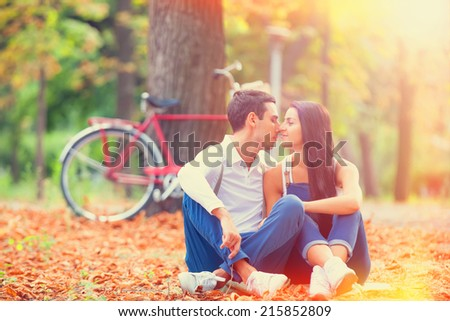 Teen couple with retro bike kissing in the park in autumn time - stock photo