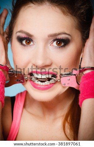 Teen crime, arrest and jail - Criminal teenager girl prisoner woman in handcuffs blue background - stock photo
