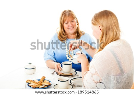 Teen daughter pouring tea for her mother at their tea party.  Isolated on white.   - stock photo