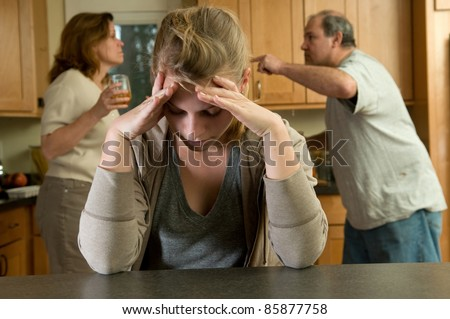 Teen daughter struggles while parents fight behind her - stock photo
