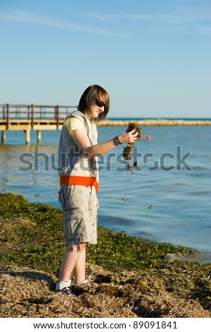 Teen disgusted at the smell of a polluted beach - stock photo