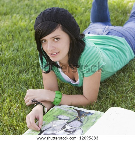 Teen draws in a sketch book while lying in grass - stock photo