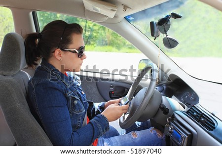 Teen drives car while distracted by text messaging on cell phone - stock photo