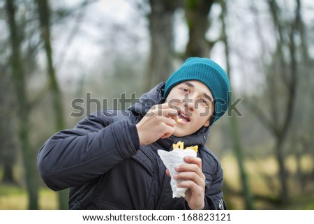 Teen eating french fries - stock photo