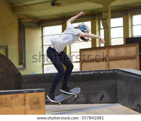 Teen female skater jumping high indoors - stock photo