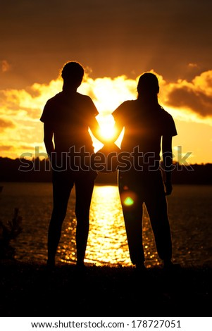 Teen Friends Pose Silhouette Lake Background - stock photo