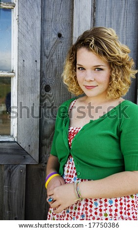 teen girl against a rustic building