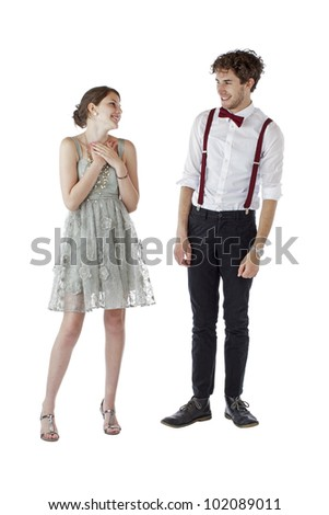 Teen girl and boy dressed formally for a prom look at each other with pleased expressions. Vertical, isolated on white, copy space. - stock photo