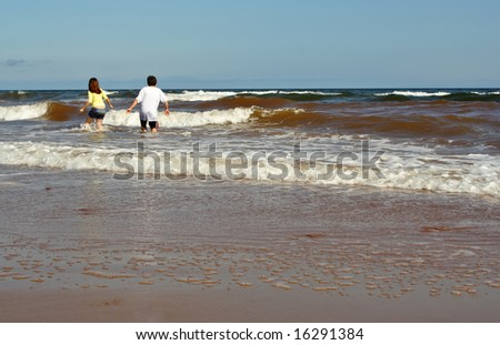 teen girl and boy walking on ocean wave at the beach