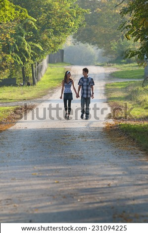 Teen girl and boy walking with holding hands and looking each other at sunset on country road - stock photo