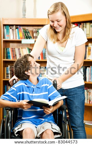 Teen girl and disabled boy in the school library. - stock photo