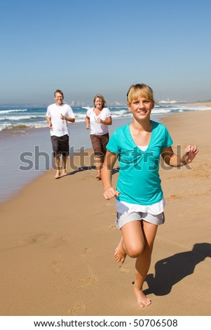 teen girl and parents running on beach - stock photo