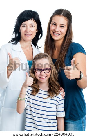 Teen girl and younger sister doing thumbs up with female doctor.